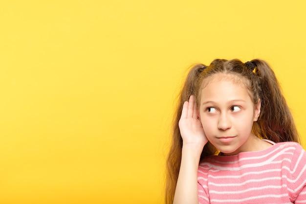 Mała dziewczynka podsłuchuje. słuchanie sekretów lub plotek. ciekawość i podważenie dziecka.