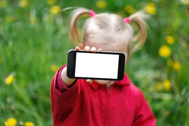 Mała dziewczynka pokaż ekran smartfona z pustą białą kopię miejsca.