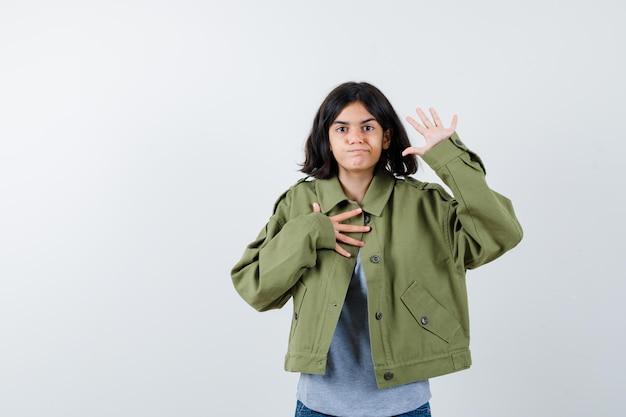 Mała dziewczynka pokazując dłoń trzymając rękę na klatce piersiowej w płaszczu, koszulce, dżinsach i patrząc pewnie, widok z przodu.