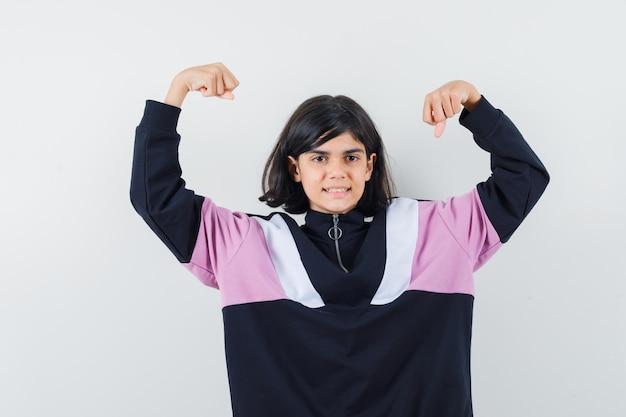 Mała dziewczynka pokazując gest zwycięzcy w koszuli i patrząc na szczęście, widok z przodu.