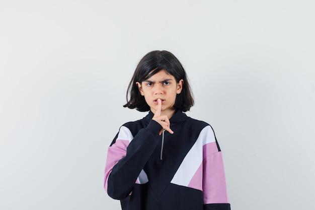 Mała dziewczynka pokazuje gest ciszy w koszuli i wygląda poważnie. przedni widok.