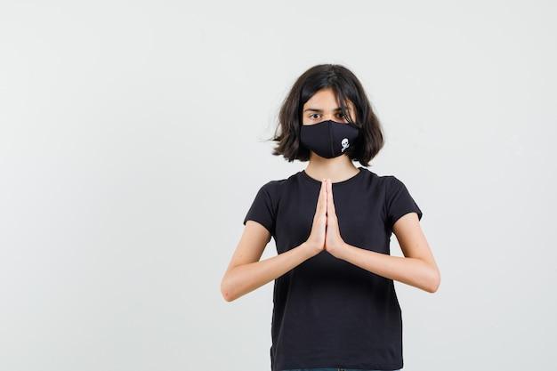 Mała dziewczynka pokazuje gest namaste w czarnej koszulce, widok z przodu maski.