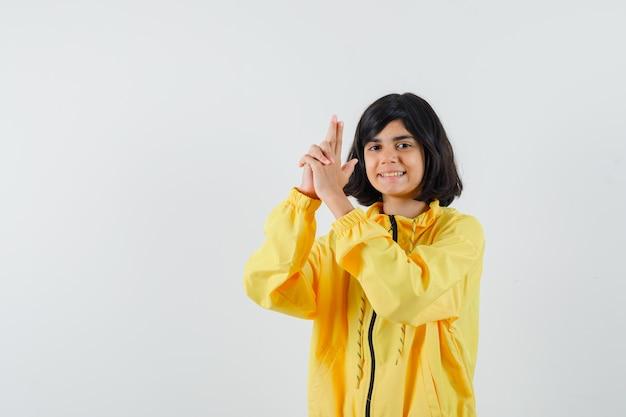 Mała dziewczynka pokazuje gest pistoletu w żółtej bluzie z kapturem i wygląda pewnie, widok z przodu.