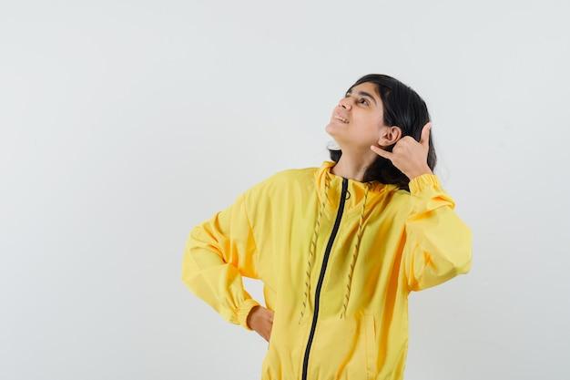Mała dziewczynka pokazuje gest telefonu w żółtej bluzie z kapturem i patrzy wesoło, widok z przodu.