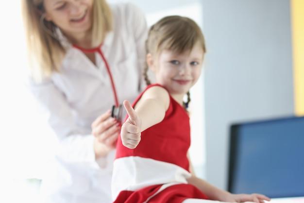 Mała dziewczynka pokazuje kciuk podczas sprawdzania lekarzy zbliżenie