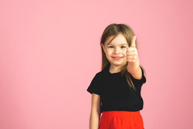 Mała dziewczynka pokazuje kciuk up na różowym tle