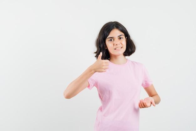 Mała dziewczynka pokazuje kciuk w górę, trzymając otwartą dłoń w różowej koszulce i wygląda wesoło. przedni widok.