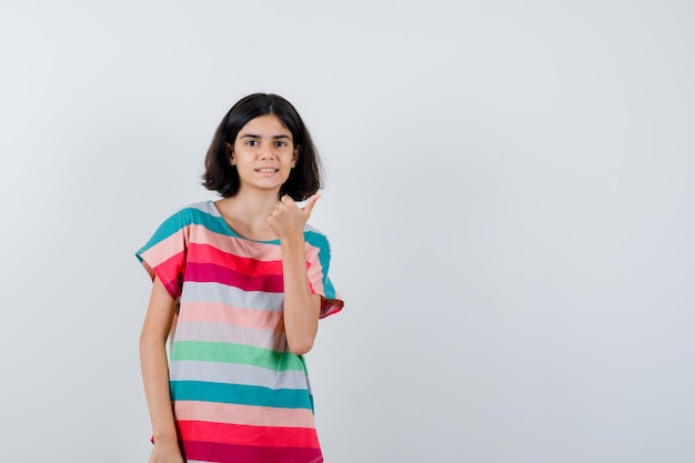 Mała dziewczynka pokazuje kciuk w t-shirt, dżinsy i szczęśliwy. przedni widok.