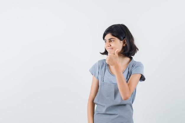 Mała dziewczynka pokazuje kciuk w t-shirt, fartuch i wesoły, widok z przodu.