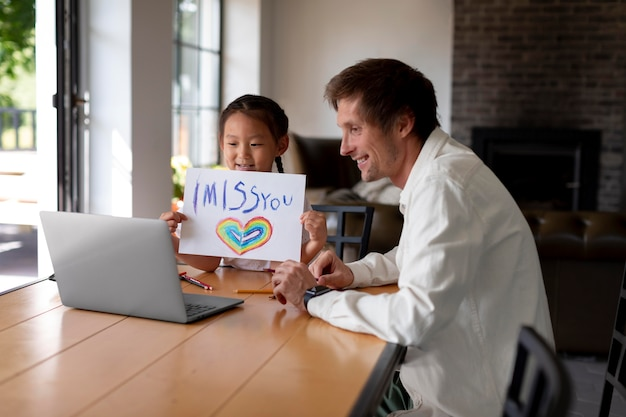"""Mała dziewczynka pokazuje mamie wiadomość """"tęsknię za tobą"""" podczas rozmowy wideo"""
