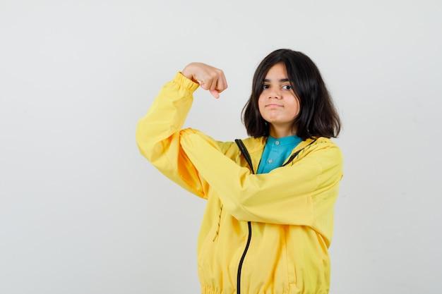 Mała dziewczynka pokazuje mięśnie ramion w koszuli, kurtce i patrząc dumny, widok z przodu.