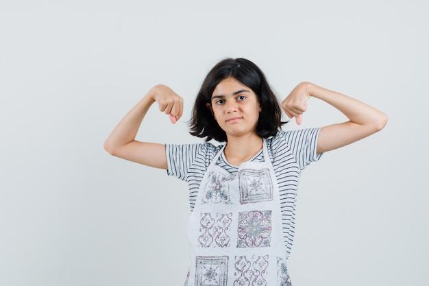 Mała dziewczynka pokazuje mięśnie ramion w t-shirt, fartuch i wygląda pewnie