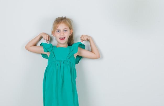 Mała dziewczynka pokazuje mięśnie w zielonej sukni i wygląda na szczęśliwą