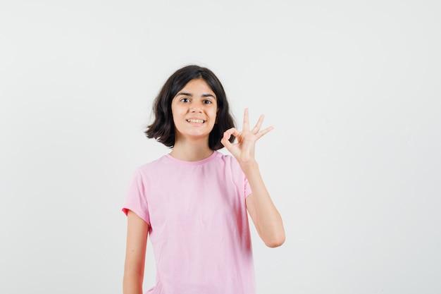 Mała dziewczynka pokazuje ok gest w różowej koszulce i wygląda jowialnie. przedni widok.