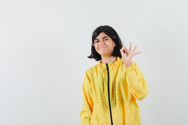 Mała dziewczynka pokazuje ok gest w żółtej bluzie z kapturem i wygląda wesoło. przedni widok.