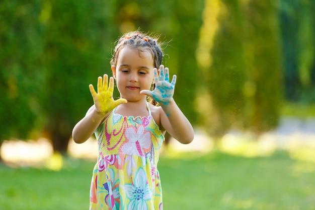 Mała dziewczynka pokazuje ona malował ręki w parku