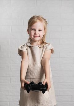 Mała dziewczynka pokazuje przy kamera joystickiem