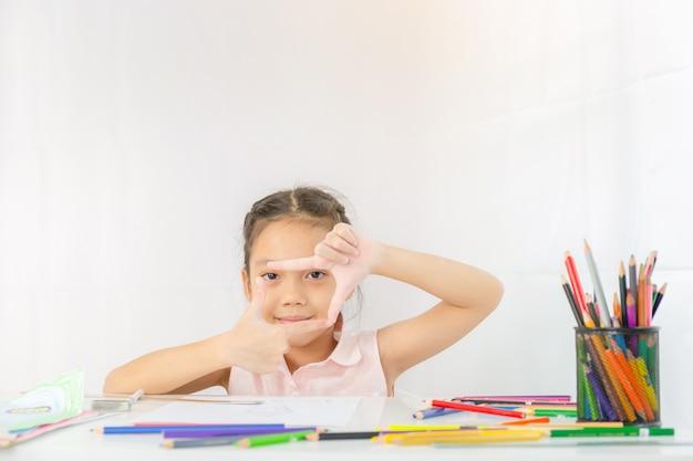Mała dziewczynka pokazuje ramkę z rąk jak zdjęcie, rysunek dziecka z kolorowymi ołówkami