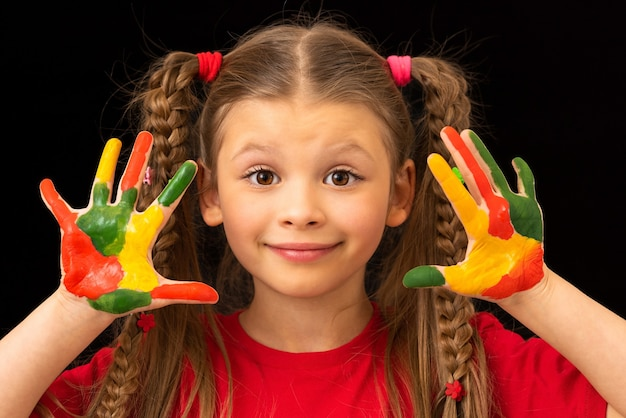 Mała dziewczynka pokazuje ręce poplamione farbami gwaszowymi.