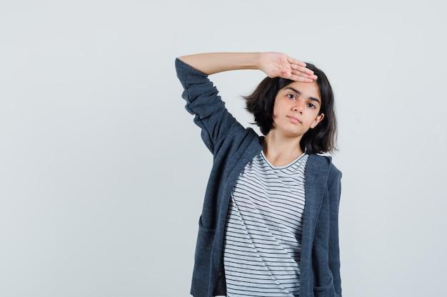 Mała dziewczynka pokazuje salutowanie gestem w koszulce, kurtce i wygląda pewnie.