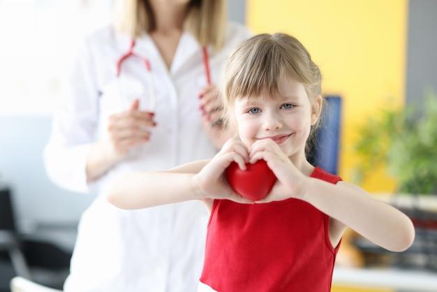 Mała dziewczynka pokazuje serce z rąk w gabinecie lekarzy