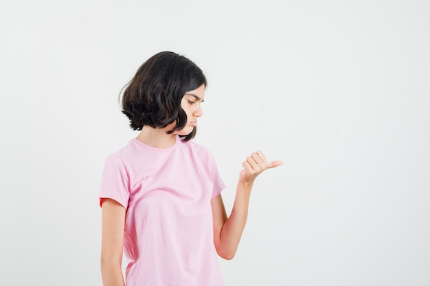 Mała dziewczynka pokazuje środkowy kciuk w różowej koszulce i wygląda zamyślony, widok z przodu.