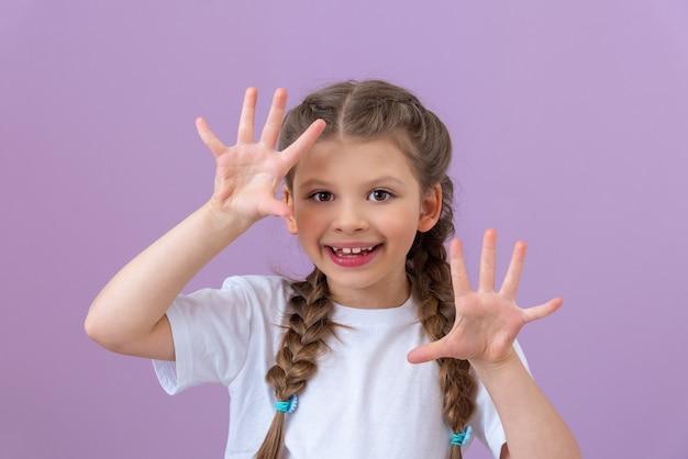 Mała dziewczynka pokazuje swoją złość rękami. na odosobnionym tle.