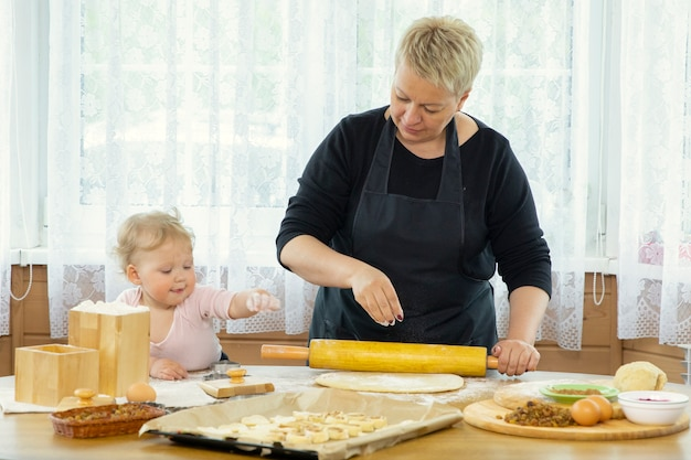 Mała dziewczynka pomaga babci rozwałkować ciasto na pizzę.