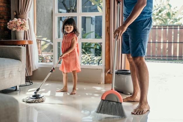 Mała dziewczynka pomaga ojcu w wykonywaniu obowiązków domowych