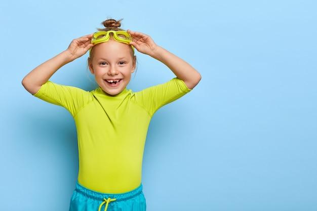 Mała dziewczynka poprawia okulary, przygotowuje się do pływania w basenie