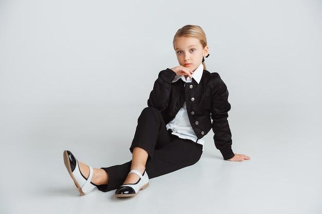 Mała dziewczynka pozuje w szkolnym mundurku na białej ścianie studia