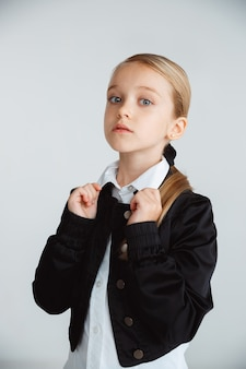 Mała dziewczynka pozuje w szkolnym mundurku z plecakiem na białej ścianie