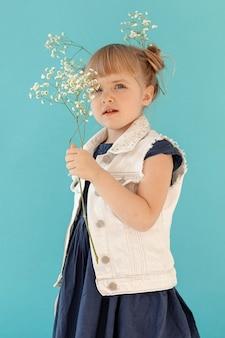 Mała dziewczynka pozuje z wiosna kwiatami