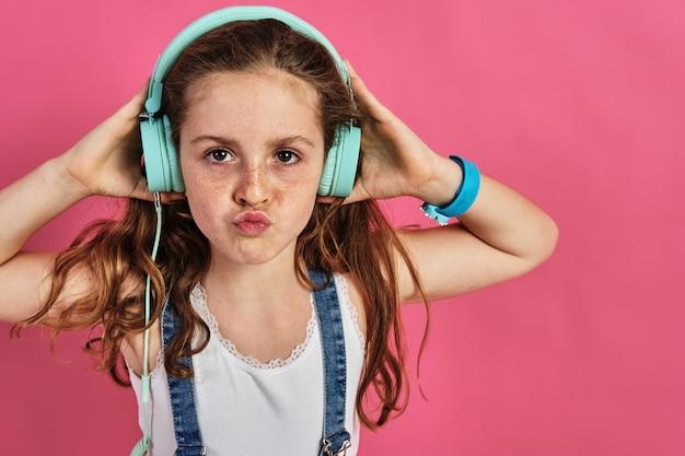 Mała dziewczynka pozuje ze słuchawkami na różowej ścianie
