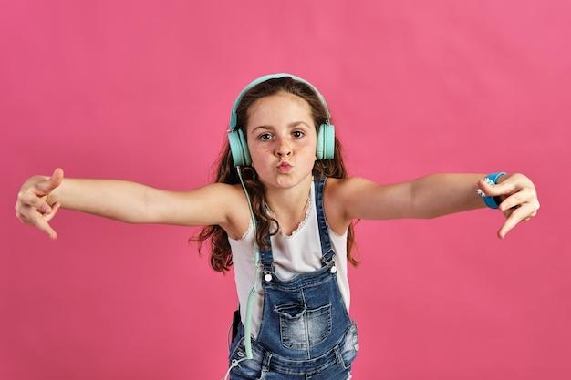 Mała dziewczynka pozuje ze słuchawkami podczas słuchania głośnej muzyki na różu
