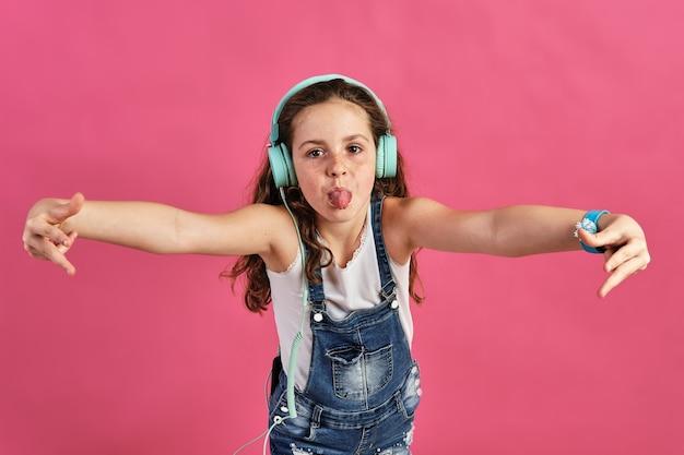 Mała dziewczynka pozuje ze słuchawkami z wystawionym językiem na różowej ścianie