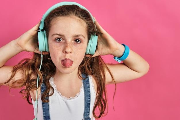 Mała dziewczynka pozuje ze słuchawkami z wystawionym językiem