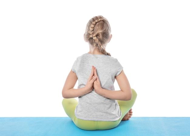 Mała dziewczynka praktykuje jogę na białym tle
