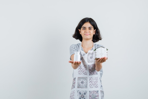 Mała dziewczynka prezentuje modelkę domu, butelkę tabletek w koszulce, fartuch i wygląda delikatnie