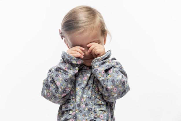 Mała dziewczynka przeciera rękoma oczy. dziecko w sukience z kwiatowym nadrukiem. zbliżenie. białe tło.