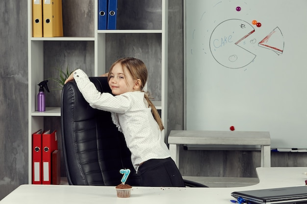 Mała dziewczynka przedstawia pracownika biurowego, bezczynnego i zachowującego się podczas pracy