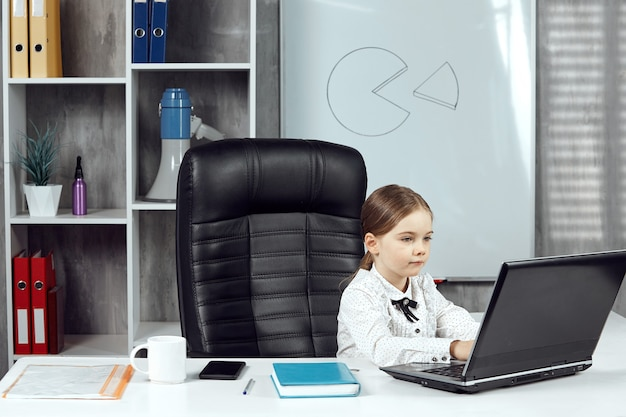 Mała dziewczynka przedstawia szefa biura pracującego przy biurku w biurze