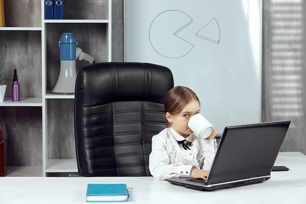 Mała dziewczynka przedstawia szefa przy białym stole, pijącego z białego kubka