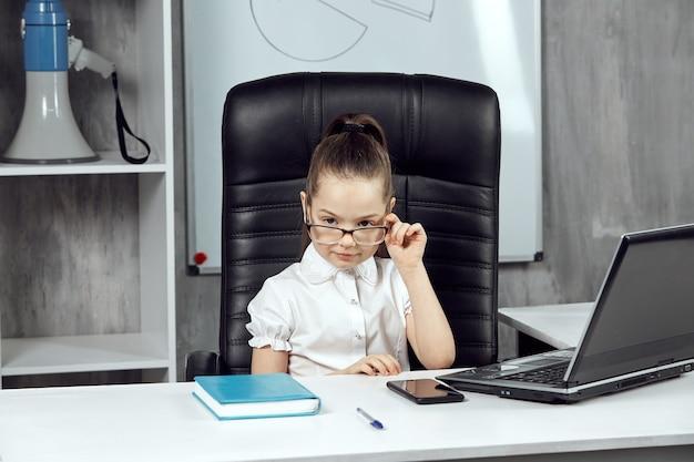 Mała dziewczynka przedstawia szefową, pozującą przed kamerą i poprawiającą okulary