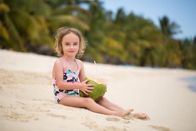 Mała dziewczynka przedszkola dziecko picie soku kokosowego na plaży oceanu.
