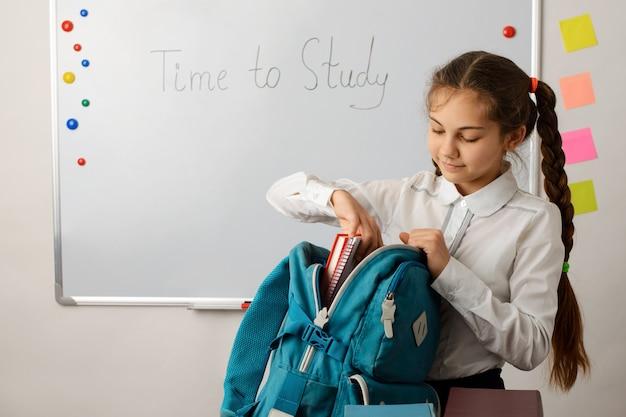 Mała dziewczynka przygotowująca się do lekcji wyjmująca zeszyty zeszyty z plecaka