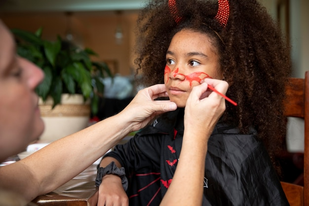 Mała dziewczynka przygotowuje się do halloween w kostiumie diabła