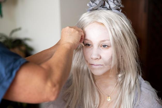 Mała dziewczynka przygotowuje się do halloween w kostiumie ducha