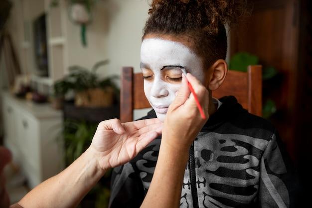 Mała dziewczynka przygotowuje się do halloween w kostiumie szkieletu