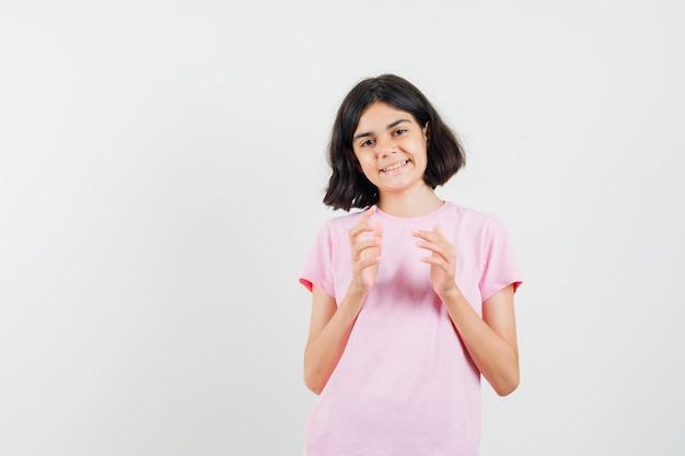Mała dziewczynka przygotowuje się do klaskać w różowej koszulce i patrząc wesoły, widok z przodu.